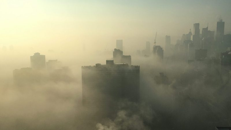 City with high-rise building covered with smog
