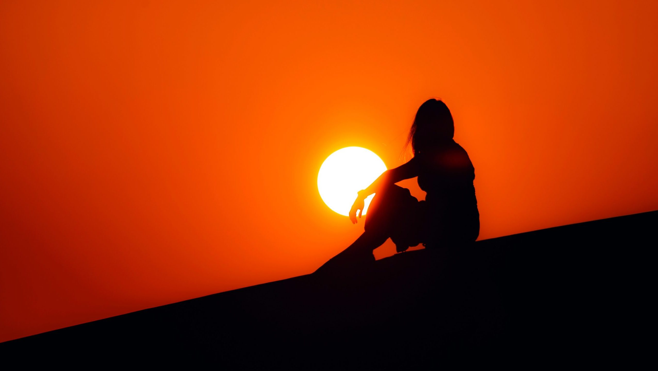 Silhouette of woman sitting on ground in front of the sun