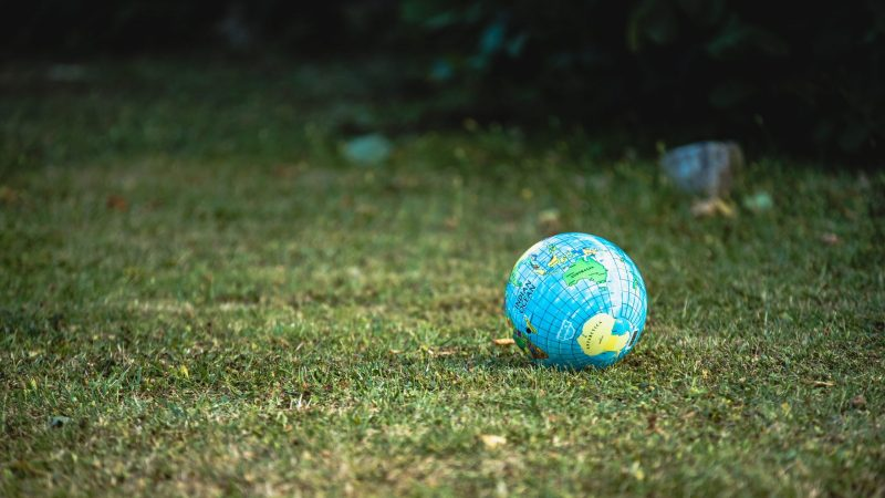 A toy Earth on a Grass Lawn
